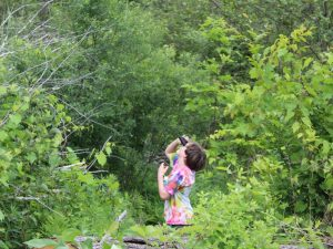 Young person with binoculars looking into a forested area