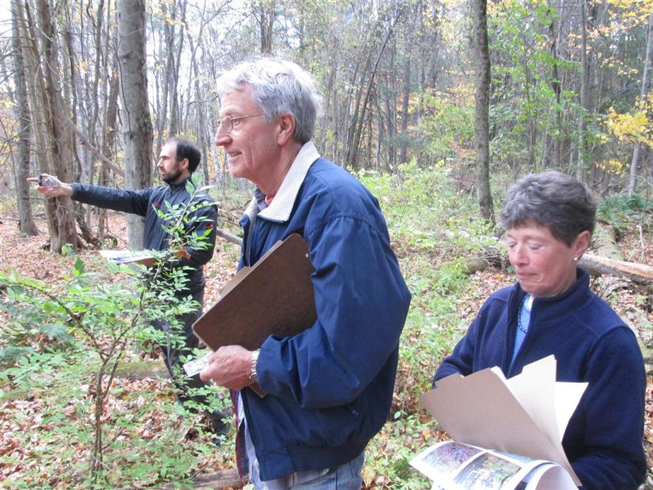 Volunteers follow a bearing through the woods.