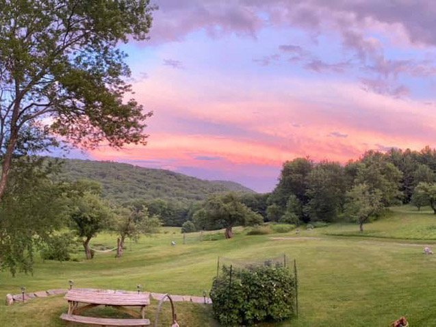 View from Warner Hill of a lawn and hills at sunset